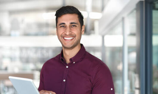Cropped portrait of a handsome young businessman using a digital tablet while standing in modern office